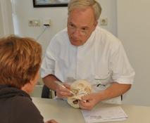 Kaakchirurg geeft uitleg aan patiënt aan de hand van schedel